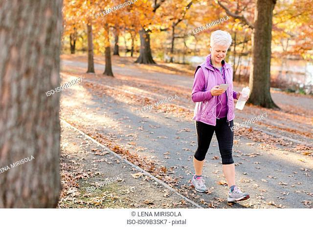 Senior woman walking outdoors, using smartphone, wearing earphones and holding water bottle