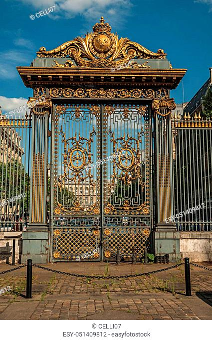 Golden iron gate and fence lavishly decorated under sunny blue sky in Paris. Known as the? City of Light?, is one of the most impressive world's cultural center