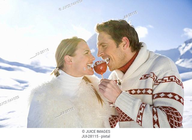 Young couple eating candy apple on winter day
