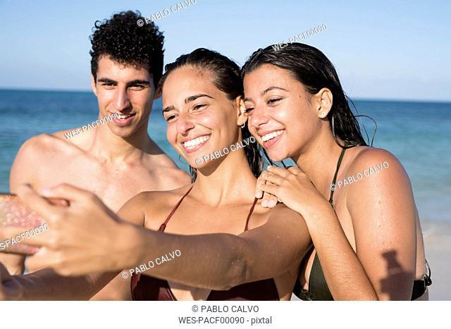 Happy friends taking selfies on the beach