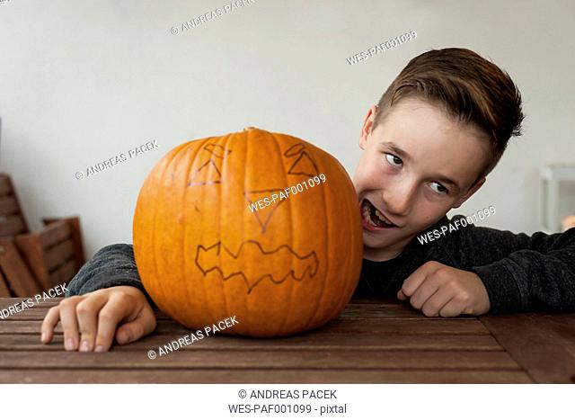 Boy making a face beside big Halloween pumpkin