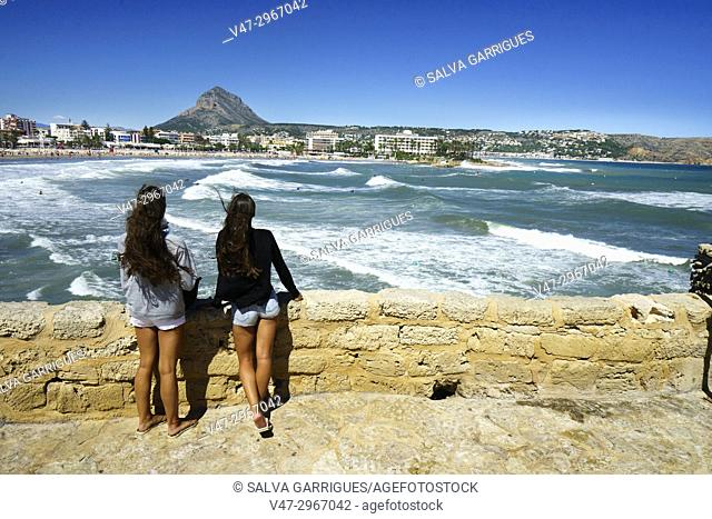 Two girls watching the waves on the beach of El Arenal in Javea, Alicante, Valencia, Spain, Europe