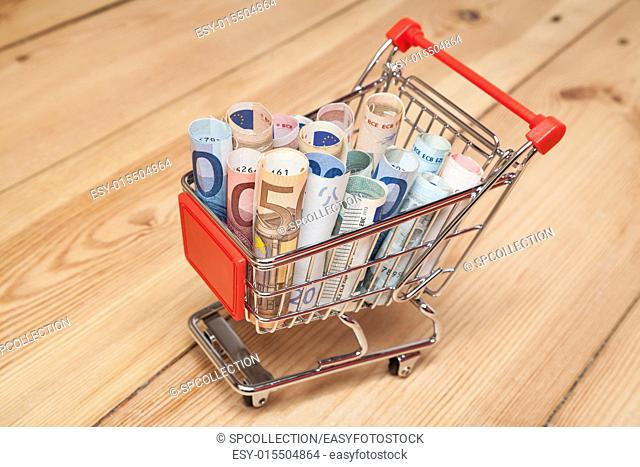 banknotes in shopping cart on wood floor