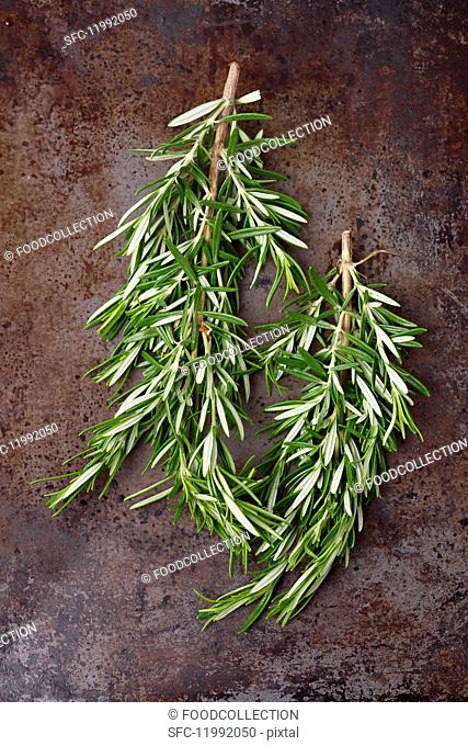 Fresh sprigs of rosemary on a metal surface