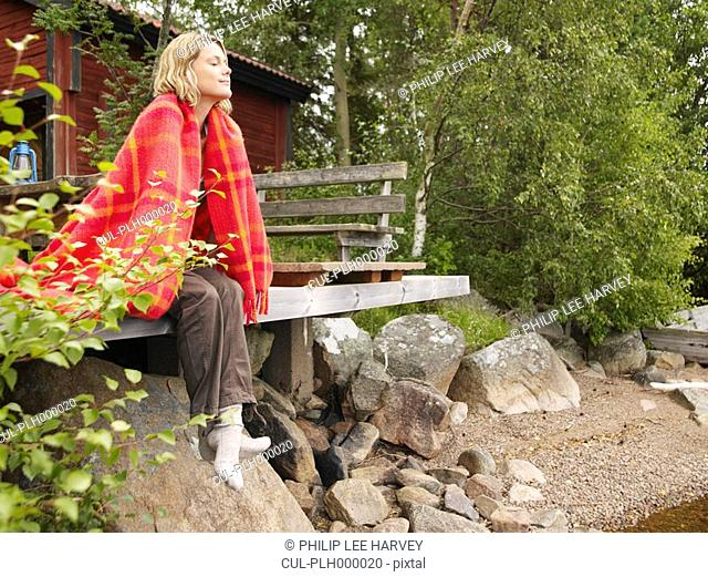 Woman with blanket wrapped around her sitting on dock smiling