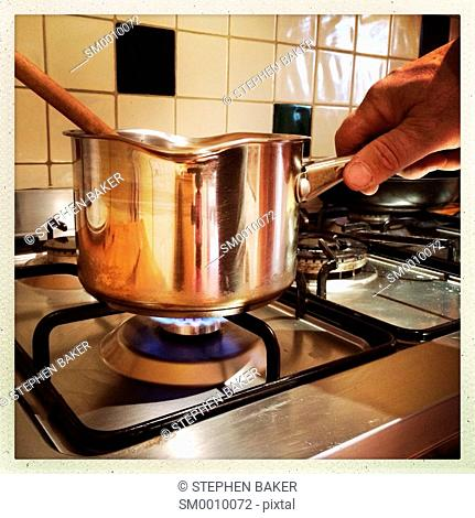 A male hand shown holding a stainless steel sauce pan over a gas hob