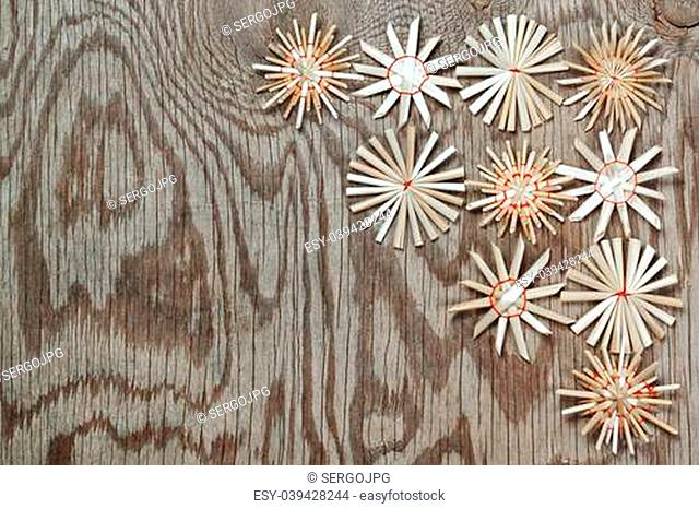 Straw Christmas snowflakes on a wooden texture