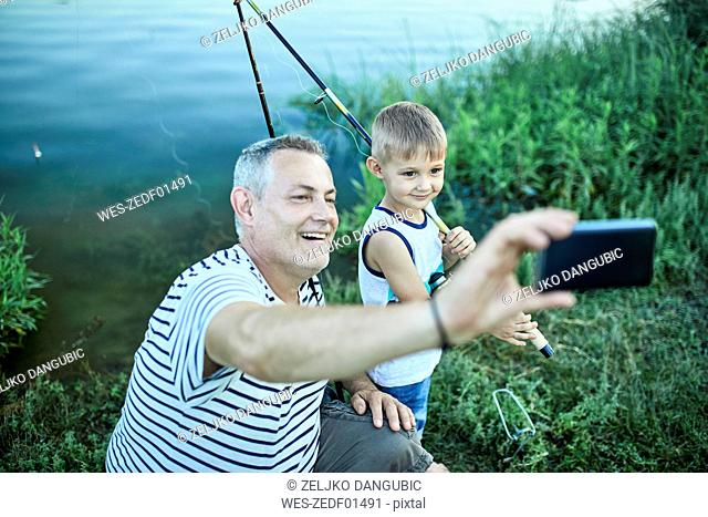 Grandfather and grandson taking selfie with smartphone at lakeshore
