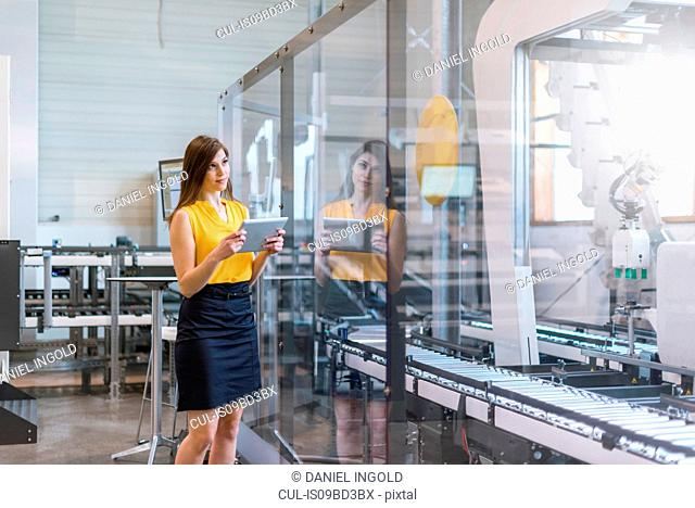 Young woman in factory, watching conveyor belt, holding digital tablet