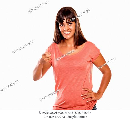 Smiling young woman pointing and looking at you on isolated background - copyspace