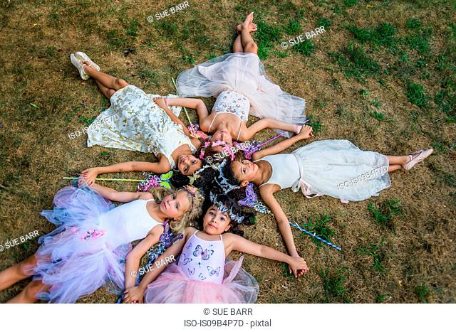 Group of young girls dressed as fairies, lying in circle, heads together