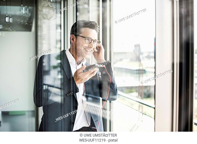 Portrait of confident businessman on the phone looking through window