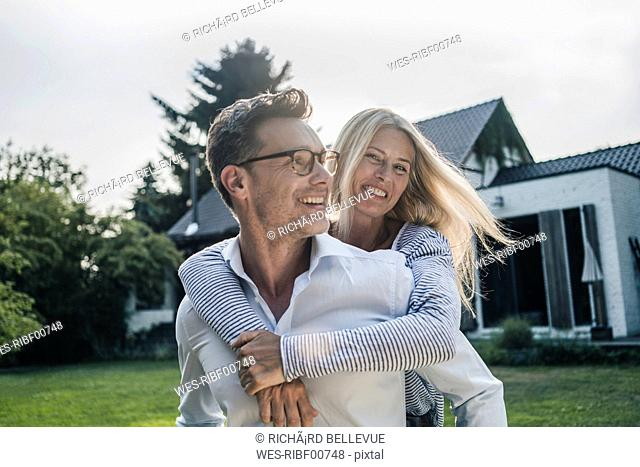Happy couple embracing in the garden of their country house