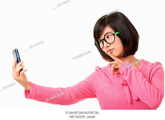 A beautiful Chinese woman using a cell phone to take a selfie on a white background