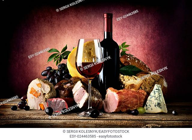 Red wine and different food on a wooden table