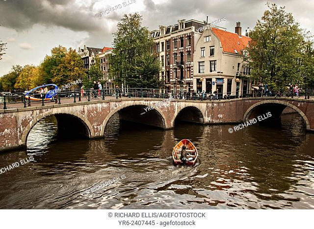 A boat passes the Hemonybrug bridge at Keizersgracht and Leidsegracht in the Singel Canel in Amsterdam