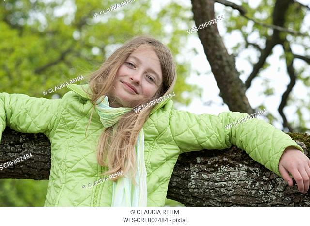Germany, Bavaria, girl leaning at a branch of a tree
