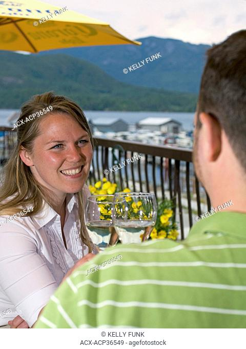 A young couple enjoys lunch and wine on a patio at a restaurant near Powell River, on the upper Sunshine coast of the Vancouver coast and mountain range