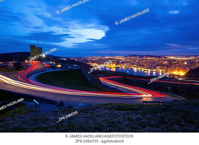Light trails created by cars as they zip up and down Signal Hill with St. John's and its harbour in the background at dusk. Newfoundland, Canada