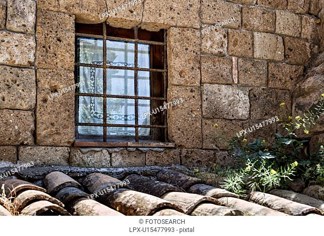 Civit?á di Bagnoregio: house detail with window above traditionally tiled roof, white lace curtain with rusty metal grate, surrounded by textured stoen wall