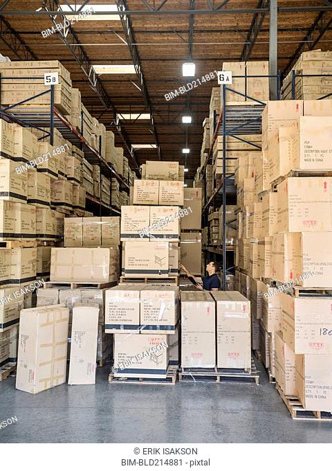 Caucasian worker examining cardboard boxes in warehouse