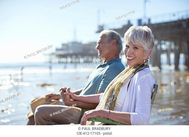 Portrait of senior couple relaxing in lawn chairs on beach