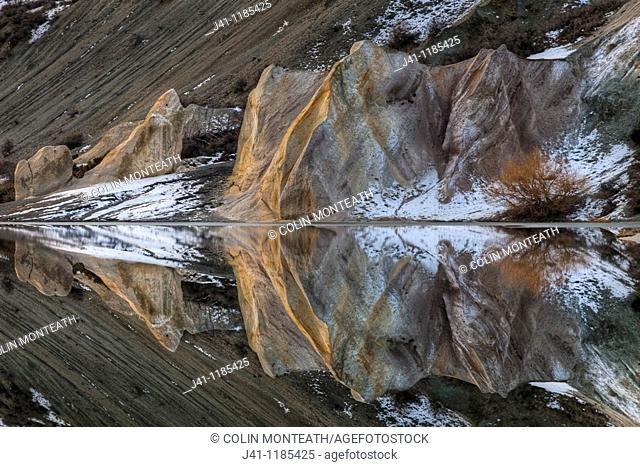 Blue Lake reflections of clay cliffs after winter storm and snowfall, St Bathans, Central Otago, New Zealand