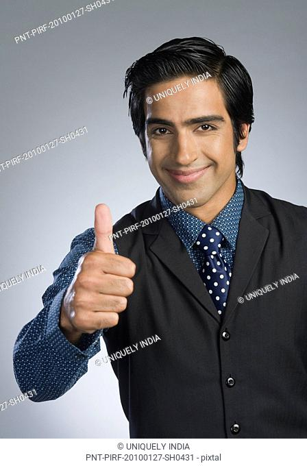 Portrait of a businessman showing thumbs up sign