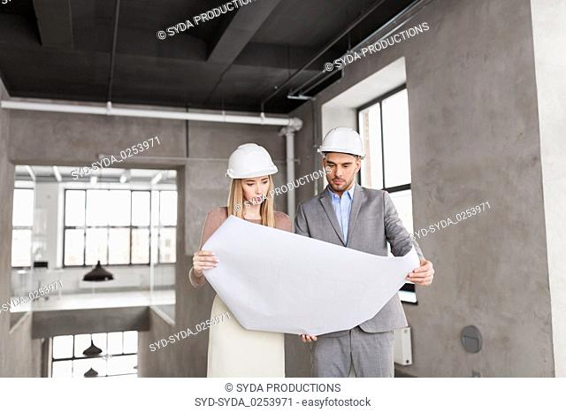 architects with blueprint and helmets at office