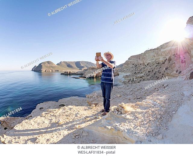 Spain, Andalusia, Cabo de Gata, man taking a selfie at the sea