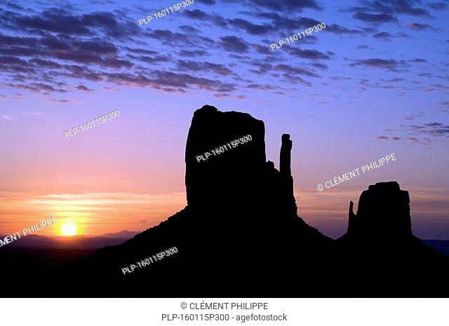 Eroded sandstone rock formations / buttes the Mittens silhouetted at dawn in the Monument Valley Navajo Tribal Park, Arizona, USA