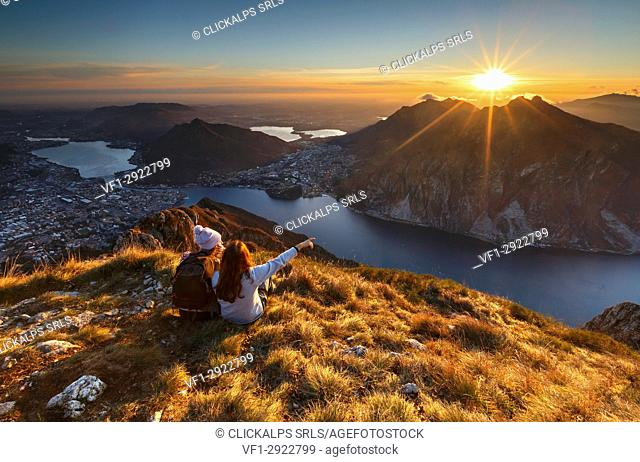Lake Como, Lombardy, Italy. Two friends watching a scenic sunset from above Lecco city