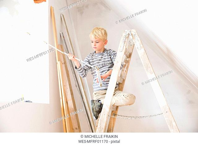 Boy with pocket rule on ladder in attic to be renovated