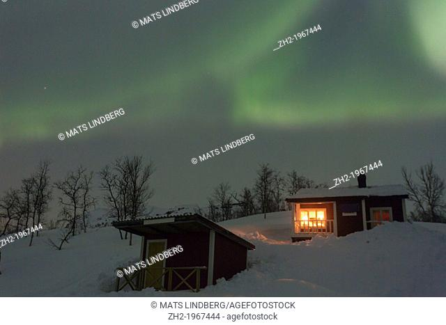 Northernlight, Aurora borealis, over a cottage with light coming through the window in winter season in march, in Riksgränsen, Swedish lapland, Sweden
