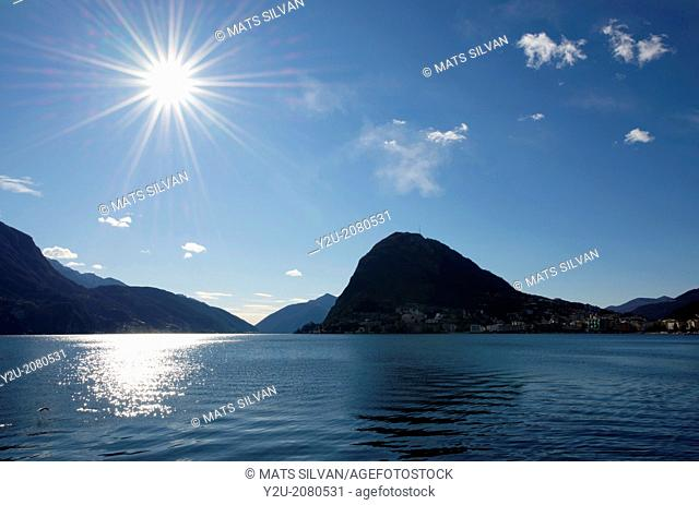 Alpine lake lugano with sun and mountain in lugano ticino switzerland