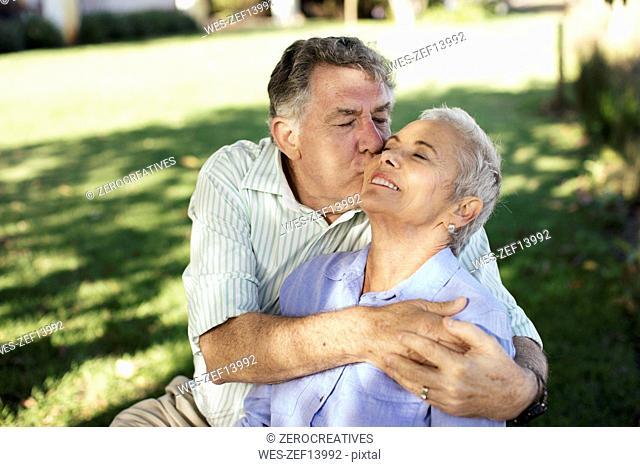 Senior man kissing his wife in garden