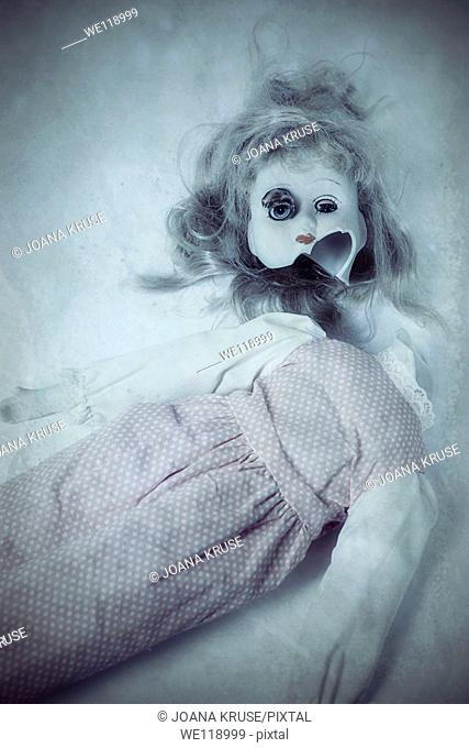 a broken doll with one eye coming out of its head