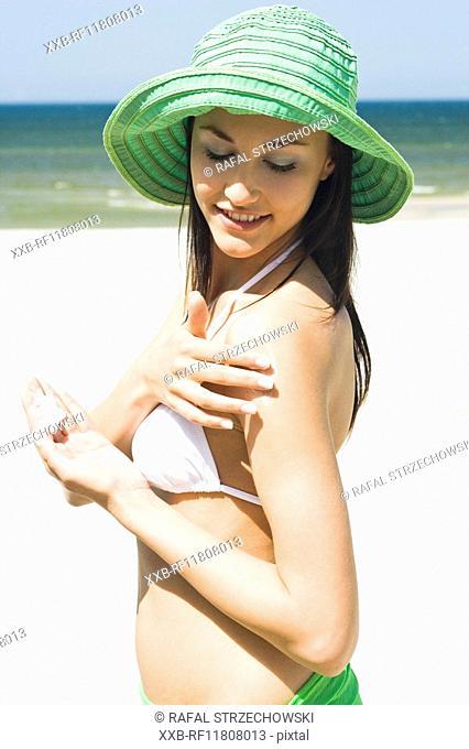woman creaming shoulders on beach