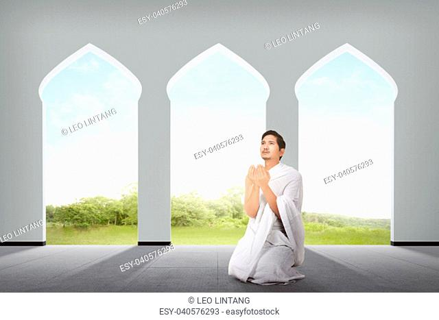 Religious asian muslim man with ihram cloth praying on the mosque