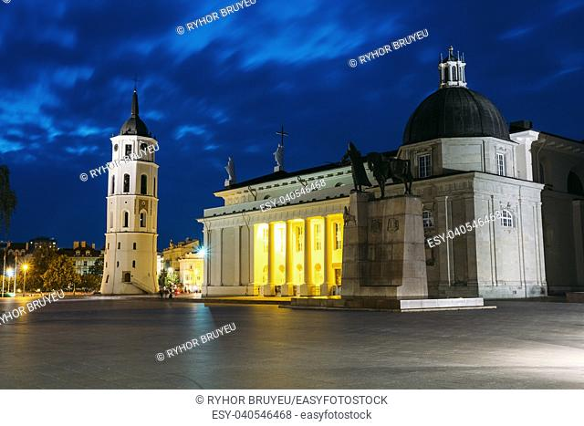 Vilnius, Lithuania. Night Or Evening View Of Cathedral Basilica Of St. Stanislaus And St. Vladislav With The Bell Tower, Blue Cloudy Sky Background