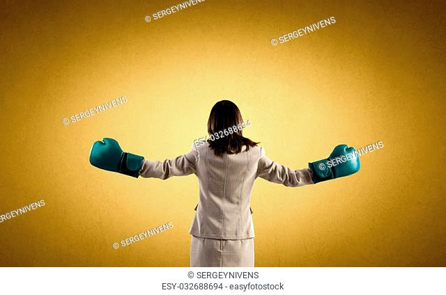Young confident businesswoman wearing blue boxing gloves