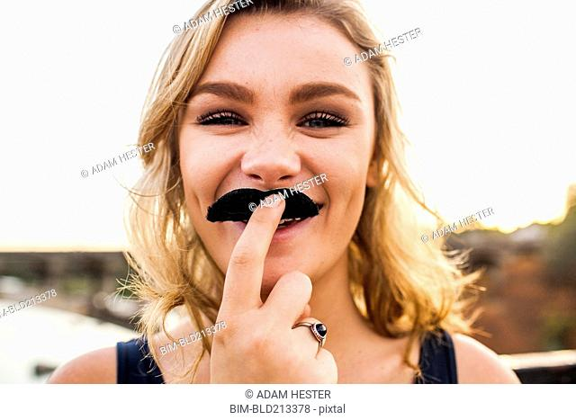 Caucasian teenage girl playing with fake mustache