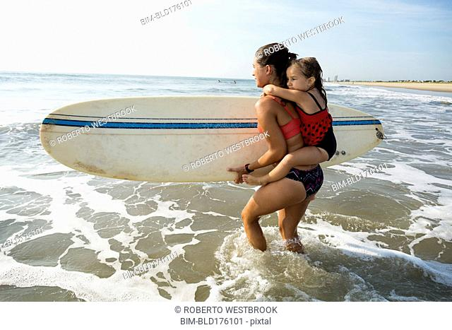 Mother carrying daughter and surfboard on beach