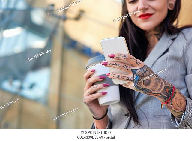 Businesswoman outdoors, holding coffee cup, using smartphone, tattoos on hands, mid section