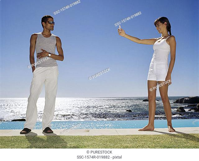 Side profile of a young woman taking a photograph of a young man at the poolside