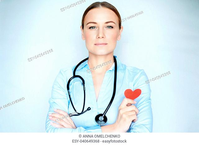 Portrait of a beautiful serious doctor with red heart symbol in hand on blue background, heart transplant center, healthy life concept