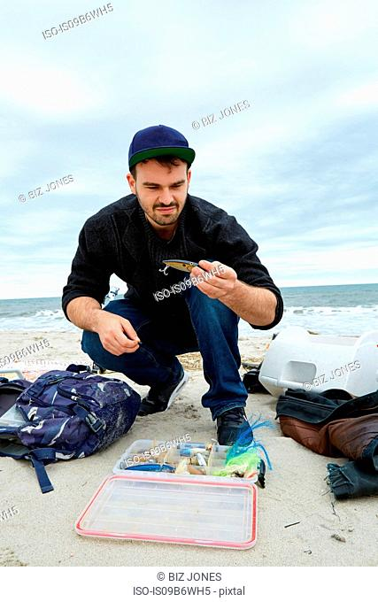 Young male sea fisher looking at hook while crouching on beach
