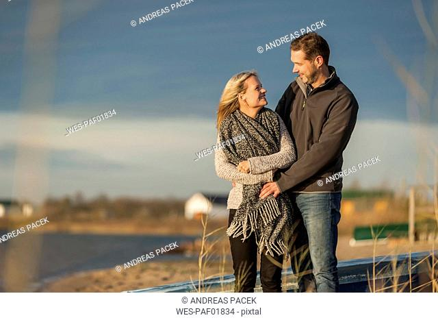 Happy couple standing at lake shore, embracing