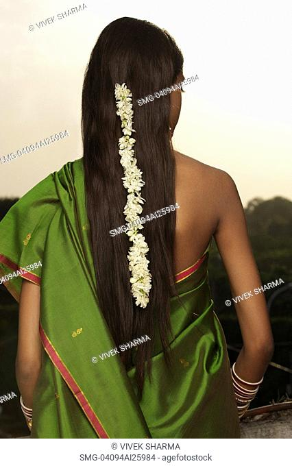 woman wearing sari with strand of jasmine blossom in her hair