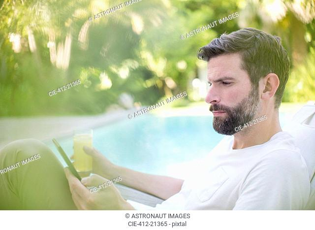 Man using digital tablet and drinking juice by swimming pool